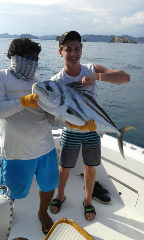 guy-holding-roosterfish-aboard-caribsea-sportfishing